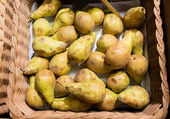 Ripe pears in basket at food market or farm — Stock Photo