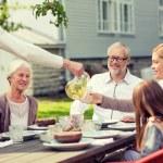 счастливая семья, имеющая праздничный ужин на открытом воздухе — Стоковое фото #76844595