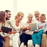 улыбающееся семейство с планшетного ПК на дому — Стоковое фото #76844715
