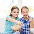 Happy girls with popcorn watching tv at home — Stock Photo #76847095
