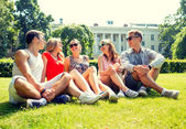 Group of smiling friends outdoors sitting in park — Stock Photo