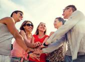 Group of smiling friends with hands on top in city — Stock Photo