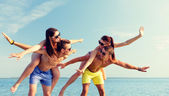 Smiling friends having fun on summer beach — Stock Photo