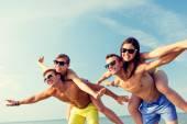 Smiling friends having fun on summer beach — Stock Photo