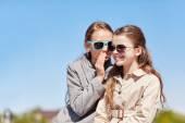 Happy girl whispering secret to her friends ear — Stock Photo