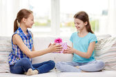 Happy little girls with birthday present at home — Stock Photo