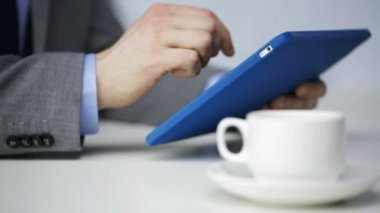 Close up of man with tablet pc drinking coffee — Stock Video