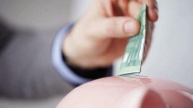 Close up of man putting money into piggy bank — Stock Video