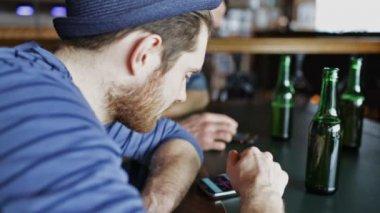Männlichen Freunde mit Smartphones trinken Bier Bar — Stockvideo