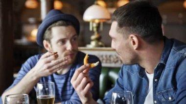 Happy mannelijke vrienden drinken bier bij bar of pub — Stockvideo
