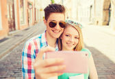 Smiling couple with smartphone in city — Stock Photo