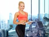Smiling sporty woman with tablet pc in gym — Foto Stock