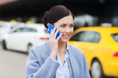 Smiling woman with smartphone over taxi in city — Stock Photo
