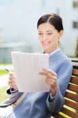 Smiling businesswoman reading papers outdoors — Stock Photo