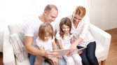 Happy family with tablet pc computers at home — Stock Photo
