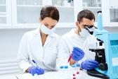 Wetenschappers met Klembord en Microscoop in lab — Stockfoto