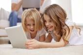 Happy little girls with tablet pc computer at home — Stock Photo