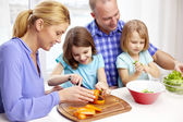 Happy family with two kids cooking at home — Stockfoto