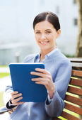 Smiling business woman with tablet pc in city — Stock Photo