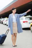 Smiling young woman with travel bag catching taxi — Stock Photo
