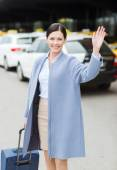 Smiling young woman with travel bag waving hand — Stock Photo
