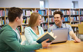 Happy students with laptop and books at library — Stock Photo