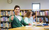 Happy student boy preparing to exam in library — Stock Photo