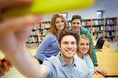 Studenten mit Smartphone Selfie in Bibliothek aufnehmen — Stockfoto