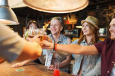 Happy friends drinking beer at bar or pub — Stock Photo