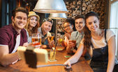 Friends with smartphone on selfie stick at bar — Stock Photo
