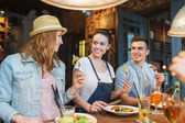 Happy friends eating and drinking at bar or pub — Stock Photo