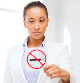 African woman with restriction no smoking sign — Stock Photo