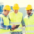 Smiling builders in hardhats with tablet pc — Stock Photo #77610874