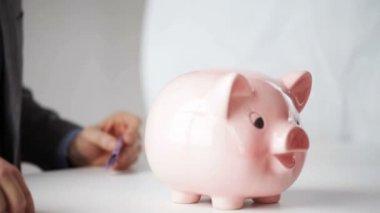 Cerca del hombre de poner dinero en la hucha — Vídeo de Stock