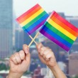 Hands holding rainbow flags over city background — Stock Photo #77926822