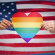 Hands with rainbow heart shape over american flag — Stock Photo #77926876