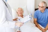 Senior woman and doctor with clipboard at hospital — Foto Stock