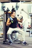 Smiling man exercising on gym machine — Stock Photo