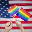 Hands with rainbow flags over american background — Stock Photo #78104034