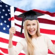 Happy student girl with diploma over american flag — Stock Photo #78104168