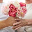Close up of senior couple with flowers — Stock Photo #78105940