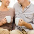Close up of happy senior couple with cups at home — Stock Photo #78105978