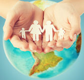 Human hands holding paper family over earth globe — Stock Photo