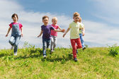 Group of happy kids running outdoors — Stock Photo