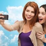 Happy teenage girls taking selfie with smartphone — Stock Photo #78204542