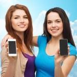 Happy young women showing smartphones screens — Stock Photo #78204546