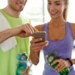 Happy woman and trainer showing smartphone in gym — Stock Photo #78206212