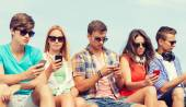 Group of friends with smartphones outdoors — Stock Photo