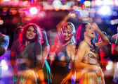 Happy friends dancing in club with holidays lights — Foto de Stock