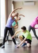 Grupo de gente sonriente que se extiende en gimnasio — Foto de Stock